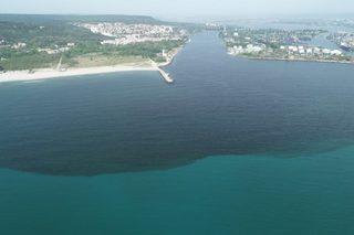 """Снимка от дрон, на варненския залив (с поглед към плавателния канал и езерото). Тъмно оцветената вода е наситена с фитопланктон цъфнал заради замърсяването с фекални води. Горе в ляво е плажът на район """"Аспарухово""""."""